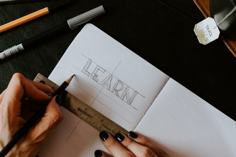 """A Pair of Hands Drawing Straight Lines on A Page Labeled """"Learn"""""""