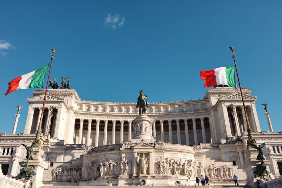 Façade of the Altaredella Patria Monument in Italy Flanked by Two Flags